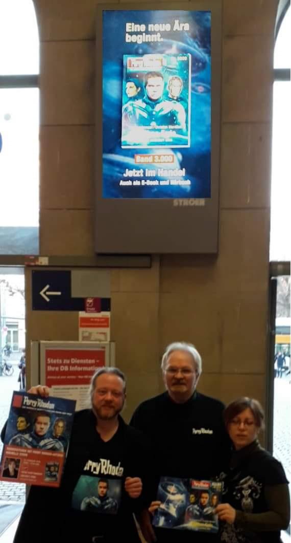 Thomas Seidel, Dieter Hofher und Michelle Stern posieren vor dem Werbebildschirm im Mainzer Hauptbahnhof. © Thomas Seidel